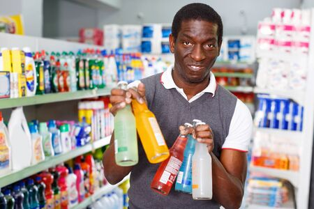 Portrait of positive smiling Afro man buying carbonated beverages in store