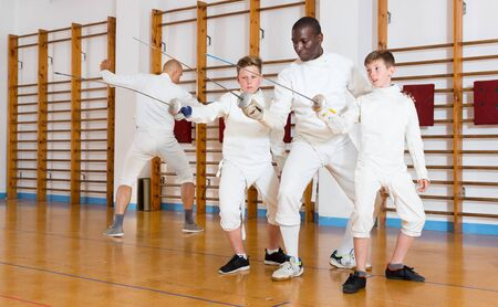 Fencing instructor explaining to young fencers effective movements and techniques in a training room