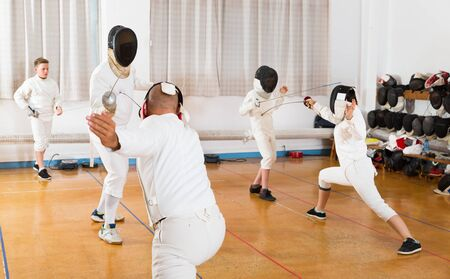 Adults and teens wearing fencing uniform practicing with foil in a gym