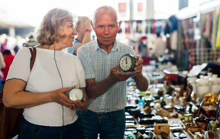 Loving senior family couple choosing vintage things on street market