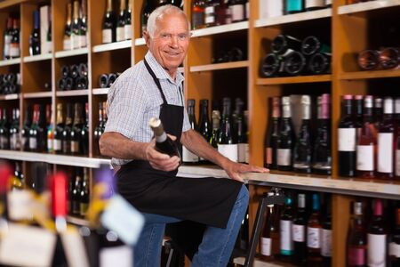 Positive male vintner holding out bottle of wine while standing on ladder near shelves in shop