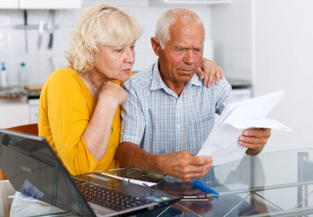 Worried mature couple with documents near laptop in home interior