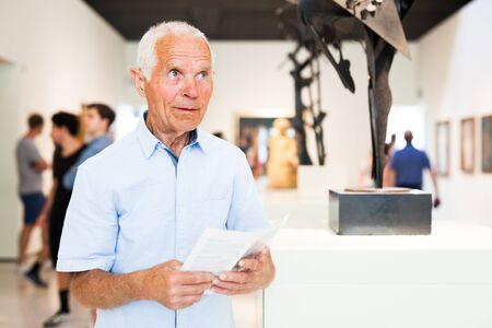 Portrait of aged man with guide brochure observing exposition in art gallery