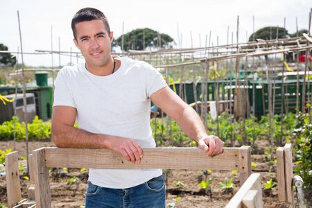 Young man professional gardener with mattock standing near trellis in garden outdoor