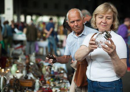 Porträt einer positiven erwachsenen Familie, die auf dem Flohmarkt nach Vintage-Waren sucht