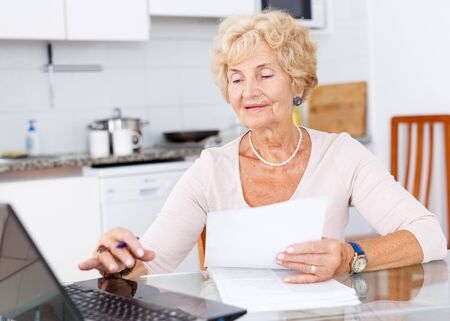 Senior woman sitting and filling up documents at kitchen table