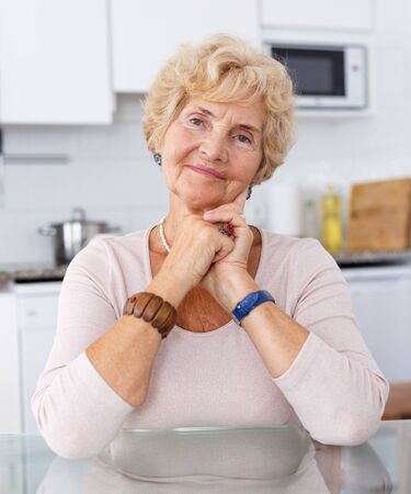 Portrait of attractive senior woman sitting at kitchen table Фото со стока