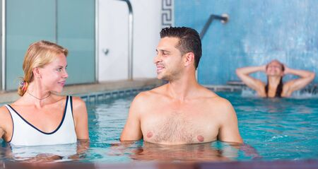 Young woman with man are talking in time resting together in pool in spa. Focus on both persons