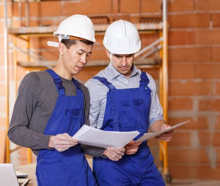 Asian and Hispanic workers holding papers with blueprints of building