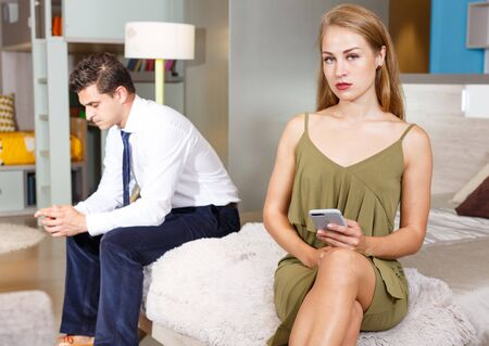 Relationship difficulties. Upset young woman sitting on bed with phone on background with frustrated boyfriend
