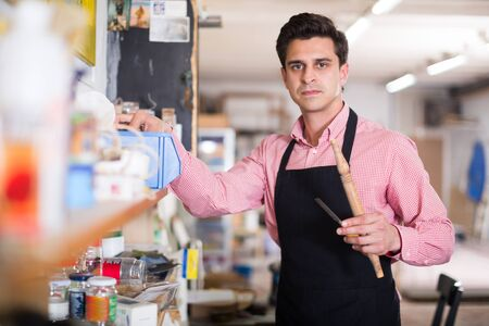 Skilled concentrated joiner looking for necessary tools on shelves in workroom