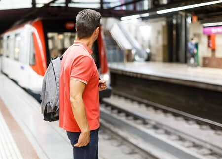 Male is traveling and waiting train on platform in the metro.
