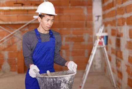 Portrait of Asian builder in process of finishing work in cottage