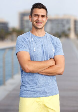 Smiling man posing after workout outdoors on urban landscape background 免版税图像