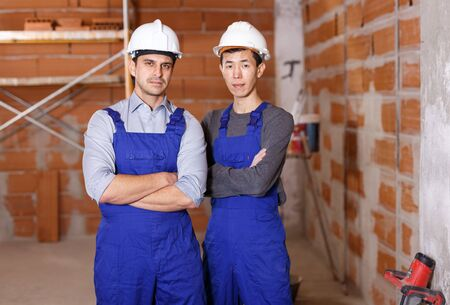 Portrait of two professional builders doing finishing work at brick cottage