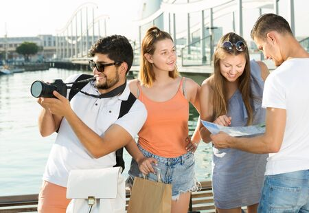 Four ordinary travelers holding map in hands and looking for their way in european town on summer day