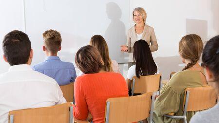 Elegante maestra dando conferencias a estudiantes en auditorio