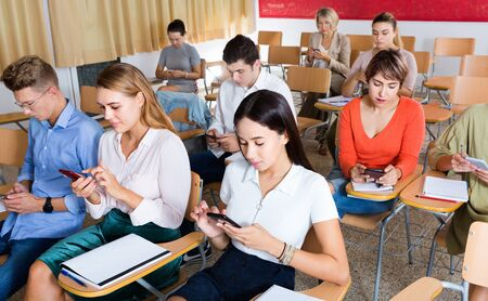 Diligent serious students using smartphones to find necessary information on lecture in university class Foto de archivo