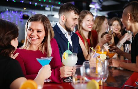 Young happy  cheerful people with cocktails having fun at nightclub