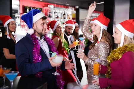 Happy young man with female friends enjoying corporate new year party in bar