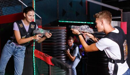 Portrait of  cheerful glad young friends standing with laser guns during laser tag game in dark room