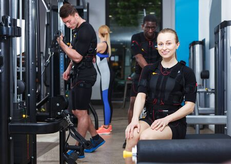Young sporty woman in EMS suit exercising in modern fitness center