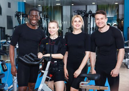 Team of confident sporty young cheerful positive people dressed EMS vests in modern fitness gym