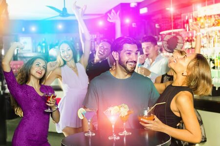 Cheerful  smiling man with young female are enjoying the party in bar.