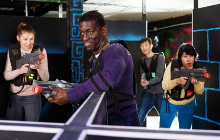 Emotional African man with laser pistol playing laser tag with friends at a dark labyrinth