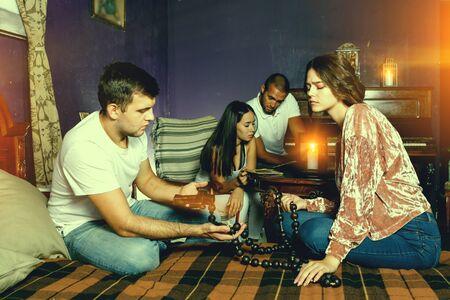 Jeunes amis regardant un chapelet en bois tout en résolvant une énigme en tant que détectives dans une salle de quête avec de vieux meubles