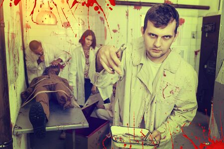 Guy having fun with friends in quest room stylized as surgical room with traces of blood, frightening with medical instruments on camera Stock Photo