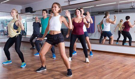 Young happy dansers studying zumba elements in dancing class Standard-Bild