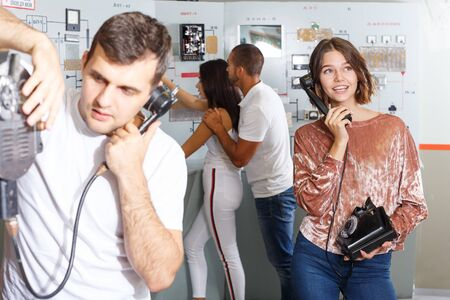 Focused girl and guy checking telephone set while trying to get out of escape room stylized as underground shelter Stock Photo