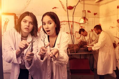 Portrait of frightened girls with friends in escape room stylized as medical room with traces of blood