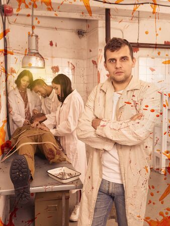 Portrait of focused guy with friends in escape room stylized as medical room with traces of blood