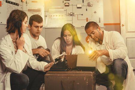 Gruppe junger Erwachsener, die versuchen, einen Fluchtraum zu verlassen, der als unterirdischer Unterstand mit Kontrolltafel stilisiert ist Standard-Bild