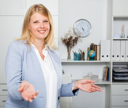 Adult smiling blond woman in business suit standing in modern office Stock Photo