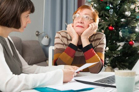 Adult daughter explaining details of document to her upset elderly mother while sitting with laptop at home table