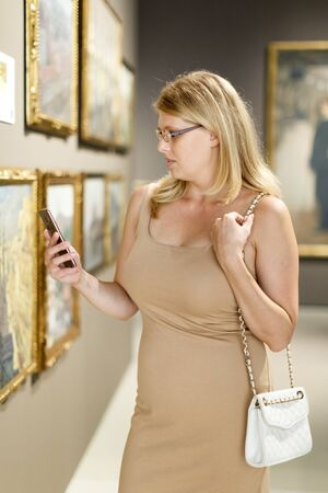 Female visitor wearing glasses looking at exhibits and taking picture on smartphone in art museum