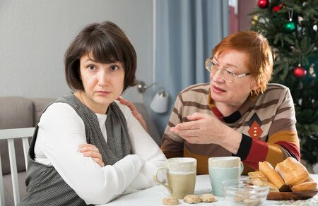 Careful loving mother comforting her upset adult daughter at home table