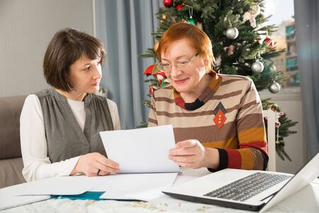 Woman social worker helping mature lady to fill up form while sitting at home on background with decorated Christmas tree
