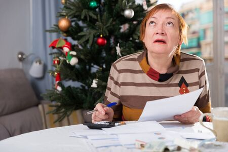 Mature woman calculates utility costs in the new year