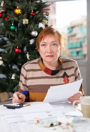 Mature woman calculates utility costs in the new year Stock fotó