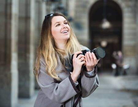 Young cheerful woman with a camera looking curious and taking a pictures outdoors