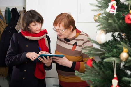 Positive mature woman answering questions of female interviewer at her home for New Year holiday Banque d'images