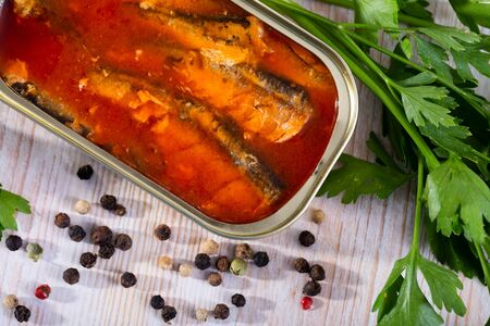 Picture of  tasty sardines in tomato sauce on background with greens and lemon Zdjęcie Seryjne
