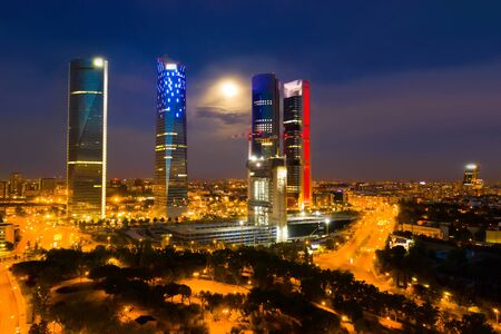 Night aerial view of modern Madrid cityscape with tallest skyscrapers of Four Towers Business Area, Spain