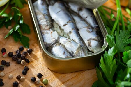 Closeup view of opened can of smoked sardines in oil on wooden table with fresh parsley, lemon and spices