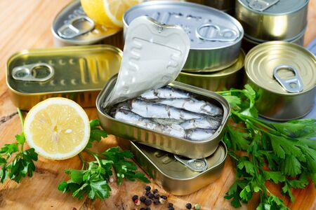 Appetizing pilchards in marinade of oil in open tin can on wooden table with greens and lemon