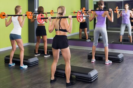 happy belgian athletic girls during workout in gym with barbell